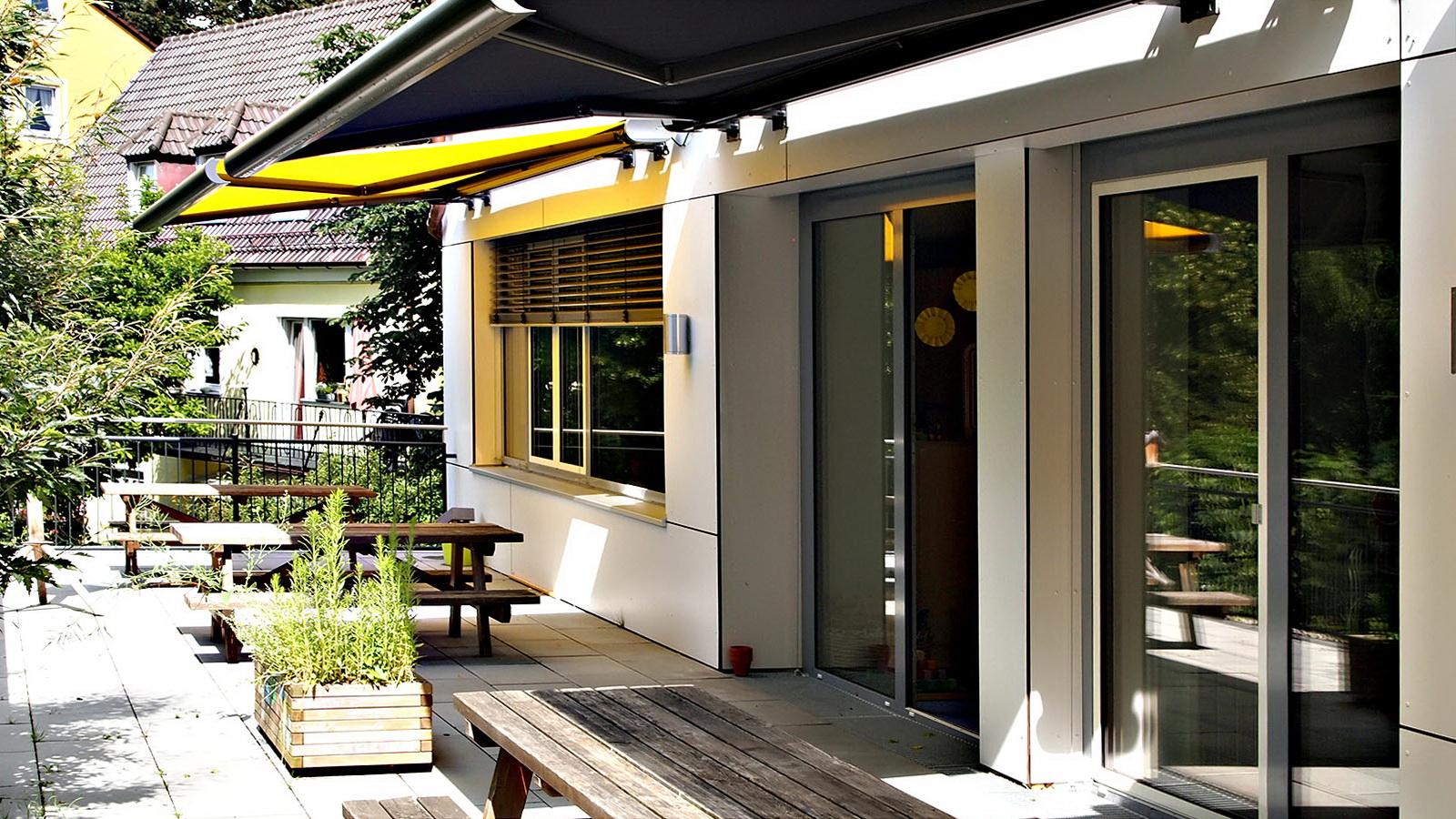 Terrasse vom Kindergarten Fruehlingsstrasse mit gelbem Sonnensegel